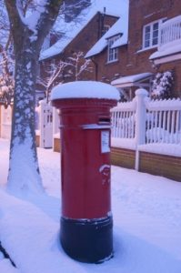 A snow covered red post box.