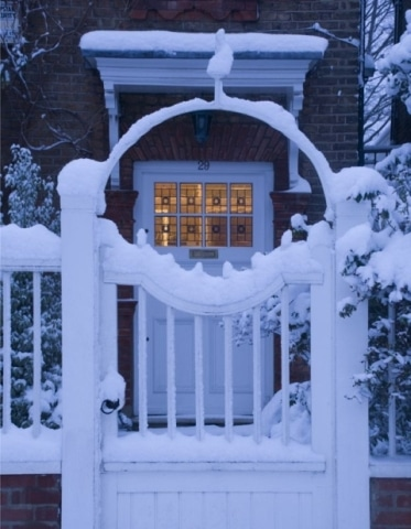 A front gate covered with early morning snow.